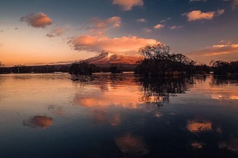 朝陽に照らされ水面に映る駒ケ岳。「七飯町から見える駒ヶ岳」など 【北海道ミライノート (47)】