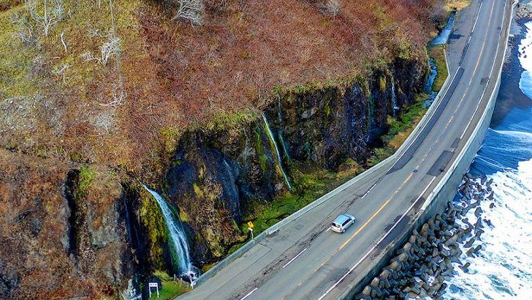道路脇の崖を流れる「フンベの滝」の不思議な光景|Domingo